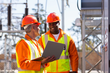 electricians using laptop computer in substation