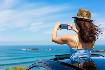Woman taking photo with smartphone camera on summer travel