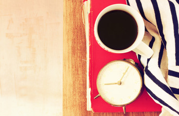 top view of coffee cup, old clock book and blanket over wooden t