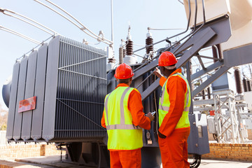 electricians standing next to a transformer