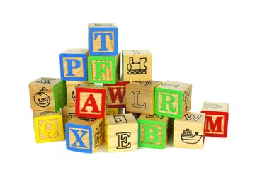 Pile of colorful toy wooden block letters over white