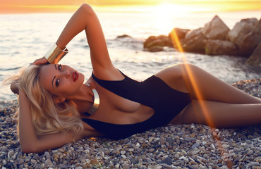 sexy girl with blond hair in swimsuit posing on sunset
