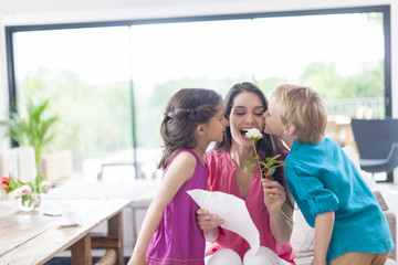 kids kissing their mother and offering a flower