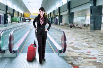 Businesswoman standing on escalator 1