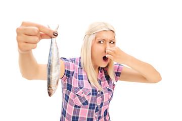 Blond woman holding a stinky fish