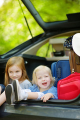 Two little sisters going to a car vacation