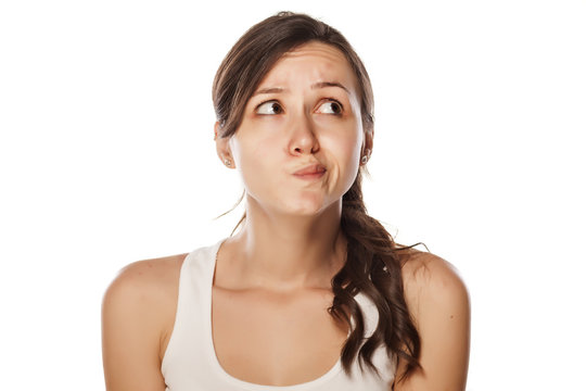 confused young woman posing on a white background