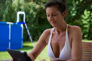 beim Pool sitzende und lesende Frau mit Tablet