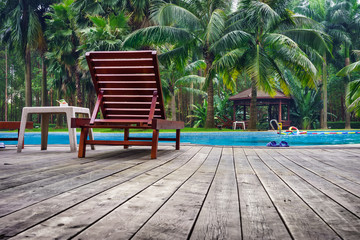 Wooden sunbath chair and side table in swimming pool