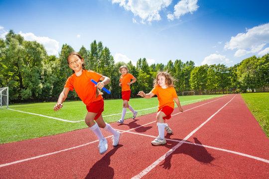 Three girls with one relay baton running