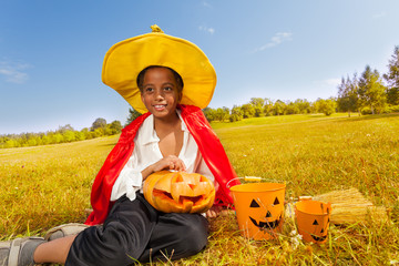 Wall Mural - Halloween boy sits on yellow grass with pumpkin