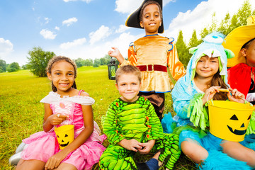 Wall Mural - Happy children in Halloween costumes sit on grass