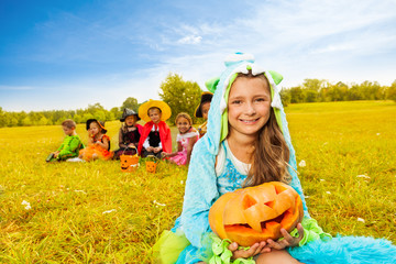 Wall Mural - Girl in monster costume holds Halloween pumpkin