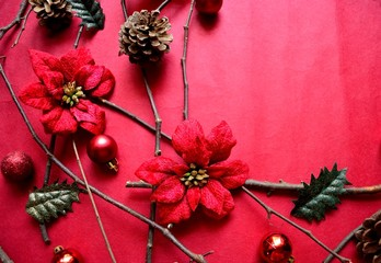 Red poinsettia with Christmas ornaments on red background