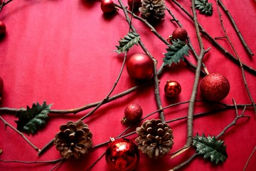 Red Christmas ornament balls with pine cones on red background