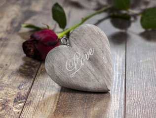 Valentine's day symbol. Heart on a wooden background with red ro