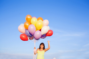 Beautiful pregnant woman girl with balloons on sky background