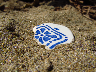 The old ceramic piece on sand surface