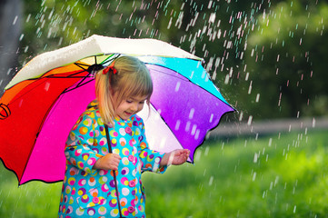 Funny cute toddler girl wearing raincoat with colorful umbrella