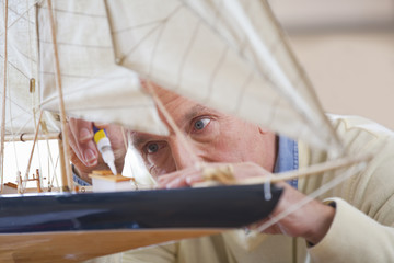 Close up of senior man applying glue to model sailboat