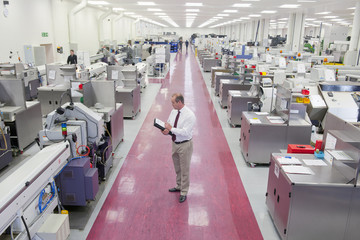 Businessman with paperwork in aisle of manufacturing plant