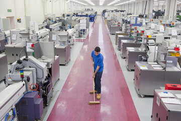 Worker with broom sweeping aisle floor of manufacturing plant