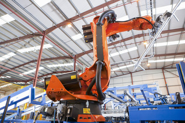 Robotic machinery lifting steel fencing on production line in manufacturing plant