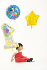Toddler girl (9-12 months) with baloons, side view