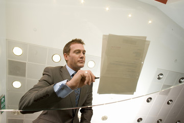 Businessman preparing to sign paperwork on glass table, low angle view through glass