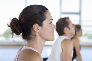 Yoga students in cobra position in class in studio, side view, close-up