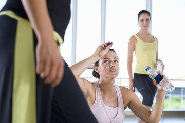 Woman with water bottle in studio in gym, wiping forehead