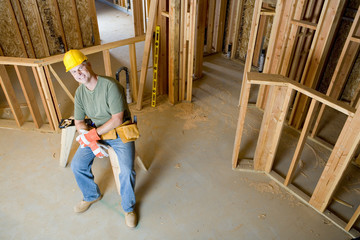 Builder on site in hardhat, smiling, portrait, elevated view