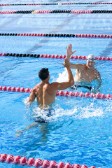 Two young male swimmers giving high-fives in swimming pool