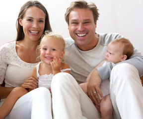 Happy family smiling at home with children