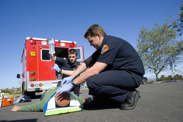 Paramedic and colleague helping man on stretcher, low angle view
