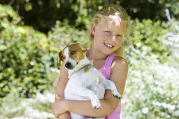 Girl (8-10) with dog outdoors, smiling, portrait