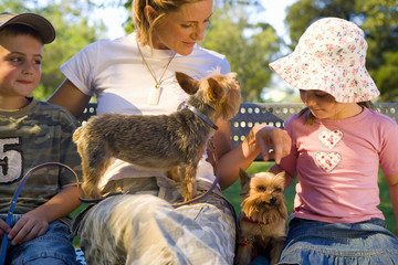 Mother on park bench with son and daughter (4-8) and dogs, close-up