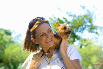 Young woman with dog on shoulders, smiling, low angle view