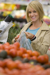 Woman choosing tomatoes in grocery store