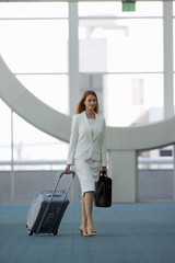 Businesswoman with rolling luggage in airport terminal