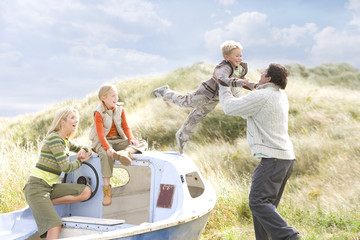 Young happy family at beach with boat