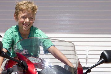 Boy sitting on motorcycle