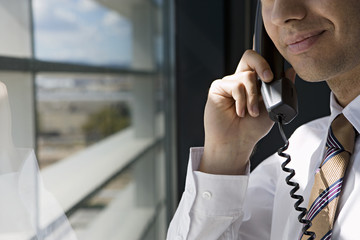 Businessman standing beside window in office, using telephone, smiling, side view, close-up