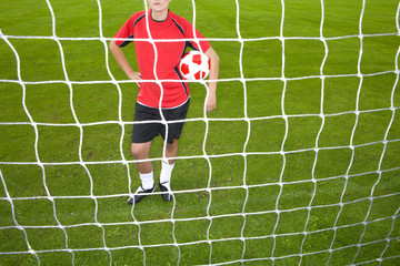 Soccer player standing at goal net