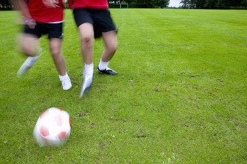 Soccer players running toward ball