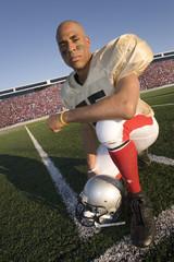 Portrait of football player kneeling on field