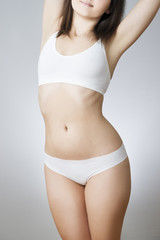 Young woman in white lingerie on a gray background