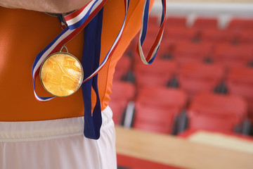 Male gymnast with gold medal, mid section