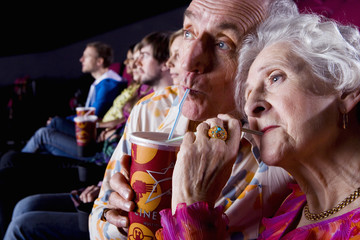 Senior couple sharing drink in cinema, close-up
