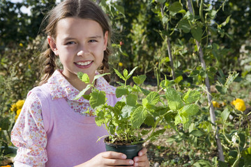 Girl (9-11) holding pot plant in garden, smiling, close-up, portrait